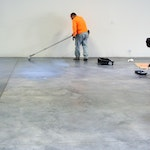Installers apply a protective topcoat over an anti-slip epoxy floor coating in a warehouse.