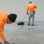 Installers apply a protective topcoat over an epoxy floor coating in a warehouse.
