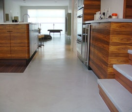 A look through the kitchen of this contemporary residence that has a modern concrete overlay installed as its flooring. (thumbnail)