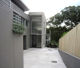 This modern looking Australian home features a concrete overlay driveway. (thumbnail)