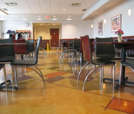 The geometric shapes and warm colors of this cafeteria demonstrate the creative versatility of polished concrete products from Duraamen. (thumbnail)