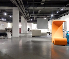 The orange of this designer chair is much brighter thanks to the subtle grey hues of the resurfaced concrete flooring. (thumbnail)