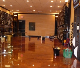 The deep copper colored floor of this wine store was created with metallic epoxy flooring. (thumbnail)