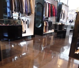 The lights and merchandise reflect on the high shine polished concrete floor in this clothing store. (thumbnail)