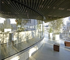 The broad daylight shows the sleek, modern, exterior concrete flooring surfaces of Stereokitchen. (thumbnail)