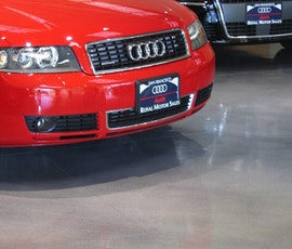 The clean modern resinous flooring of this San Francisco auto dealer let's their cars shine. (thumbnail)