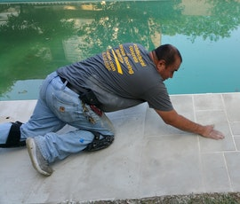 Finishing touches by hand to this walkway around the swimming pool.  (thumbnail)