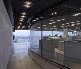 Stereokitchen Bar & Restaurant as viewed from an outdoor corridor. The smooth, modern look of the concrete overlay flooring helps accentuate contemporary look of the round glass walls. (thumbnail)