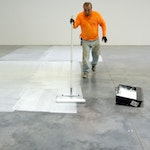 Installer applying a clear topcoat to a concrete floor in a warehouse. Duraamen's warehouse in Cranbury NJ.