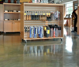 The metallic epoxy flooring enhances the product display as it's reflected of its surface. (thumbnail)